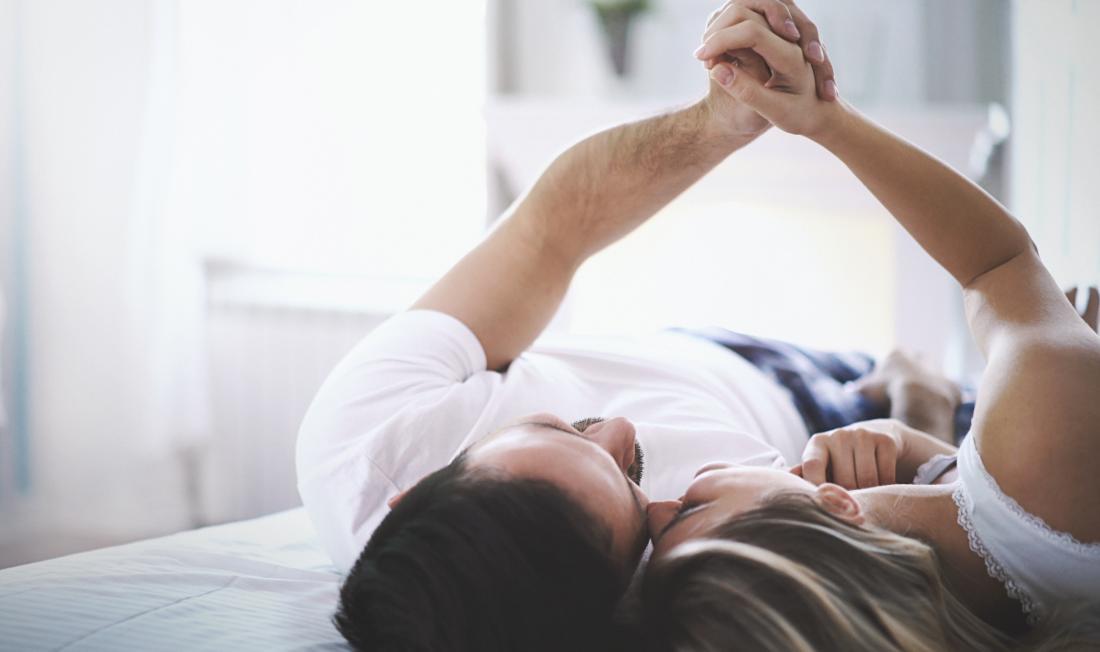 casal de mãos dadas na cama