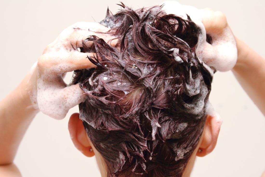 Persona che lava i capelli con shampoo e balsamo.