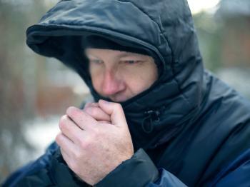 Um homem sopra as mãos para ficar aquecido
