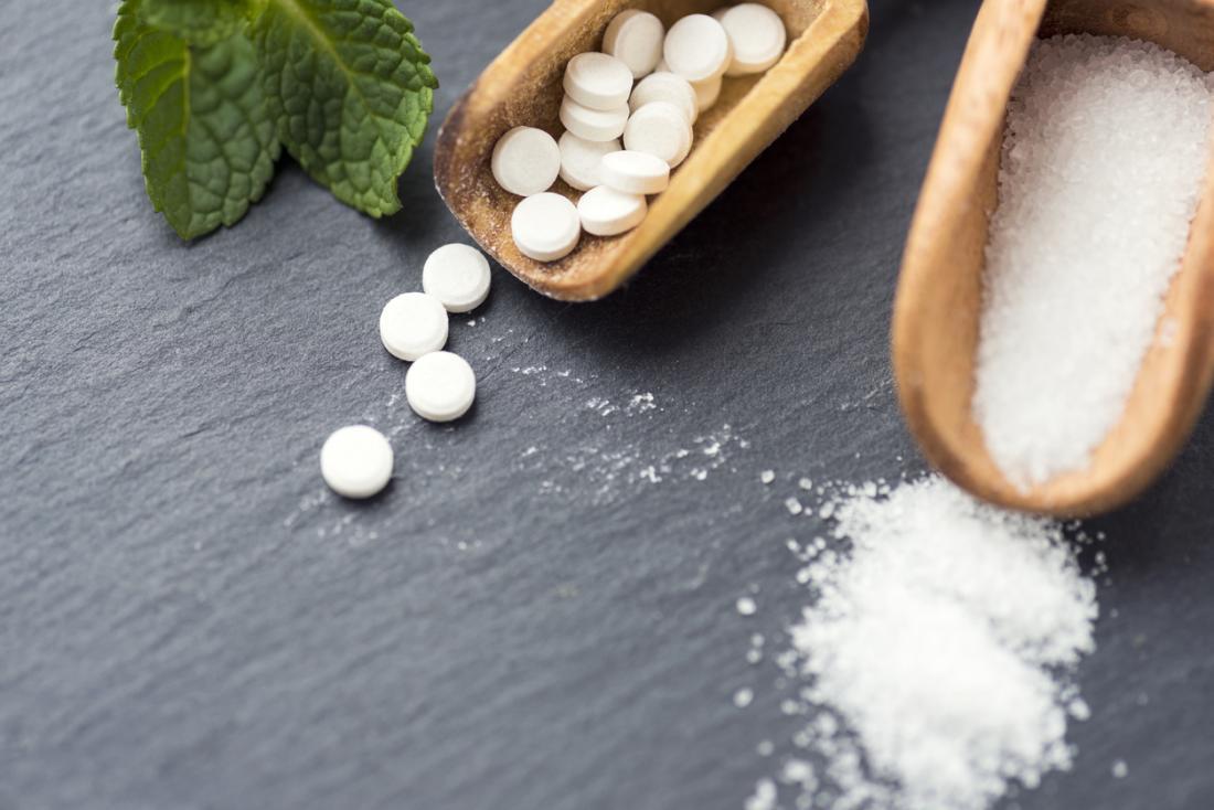 Pillole di stevia e sorriso sui cucchiai di legno, accanto alla foglia dalla pianta di stevia.