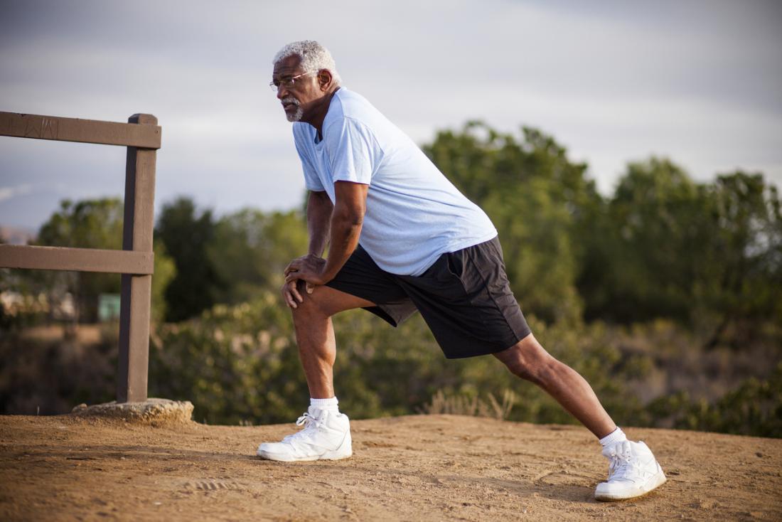 Старши мъж, протягащ мускулите на краката преди тренировка.