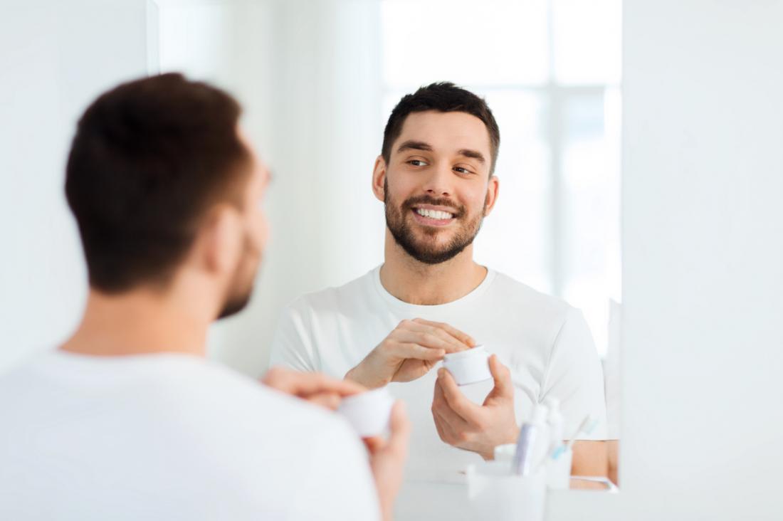 човек овлажнява лицето си