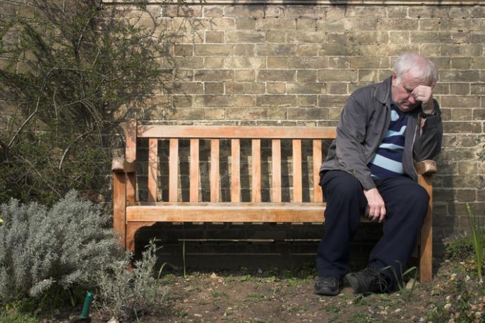 Vieil homme assis sur un banc à la recherche perdu