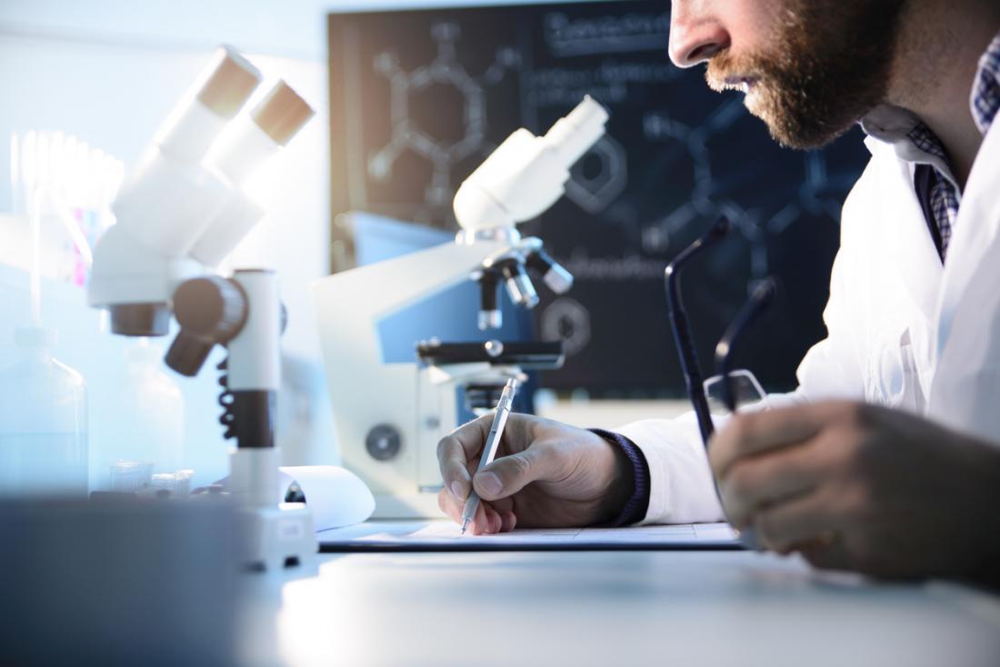 Forscher, der ein Mikroskop untersucht.