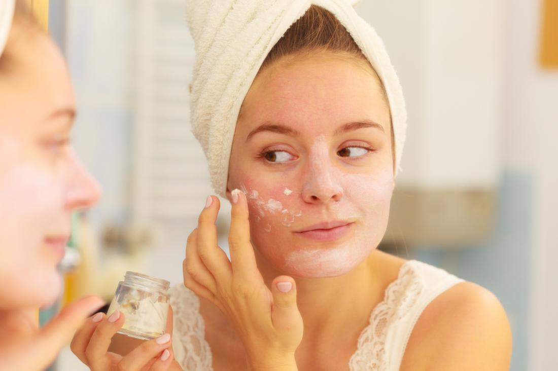 [giovane donna che applica la crema per il viso sulla pelle secca]
