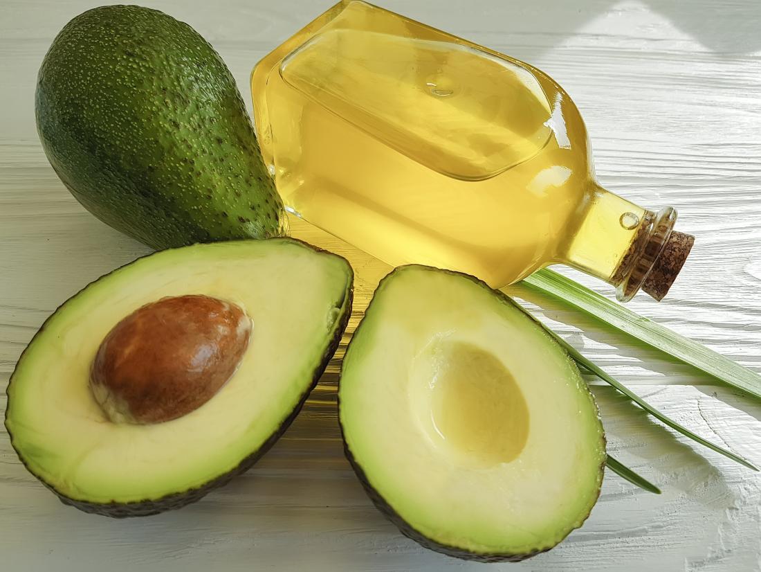 Óleo do abacate no frasco ao lado do abacate partido ao meio.