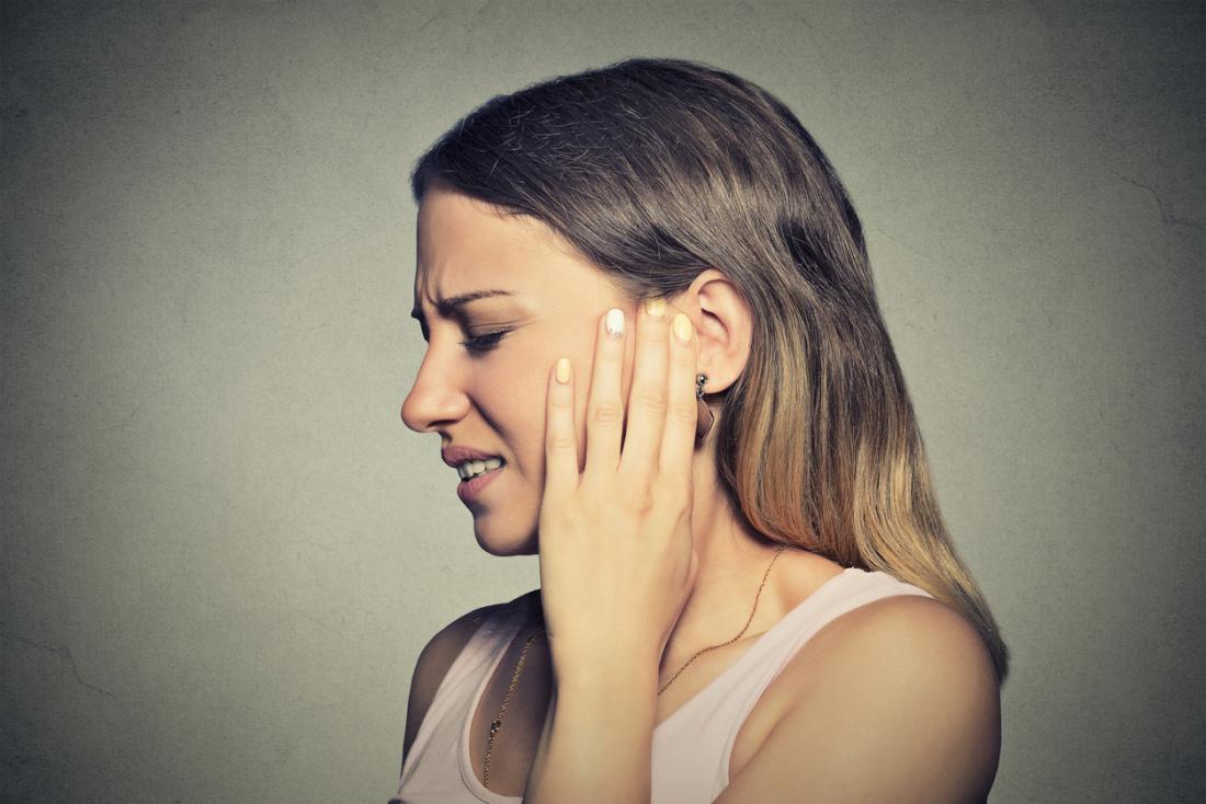 Femme tenant son oreille gauche dans la douleur à cause d'une infection.