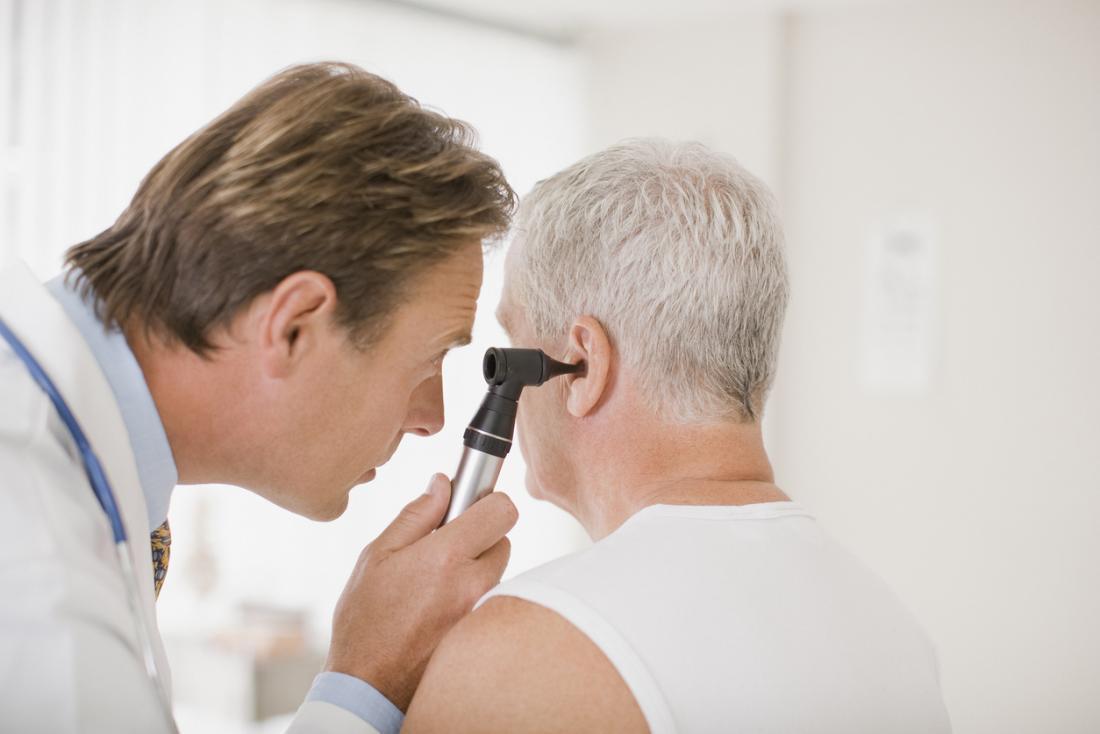 Médecin effectuant un examen de l'oreille sur un patient masculin senior.