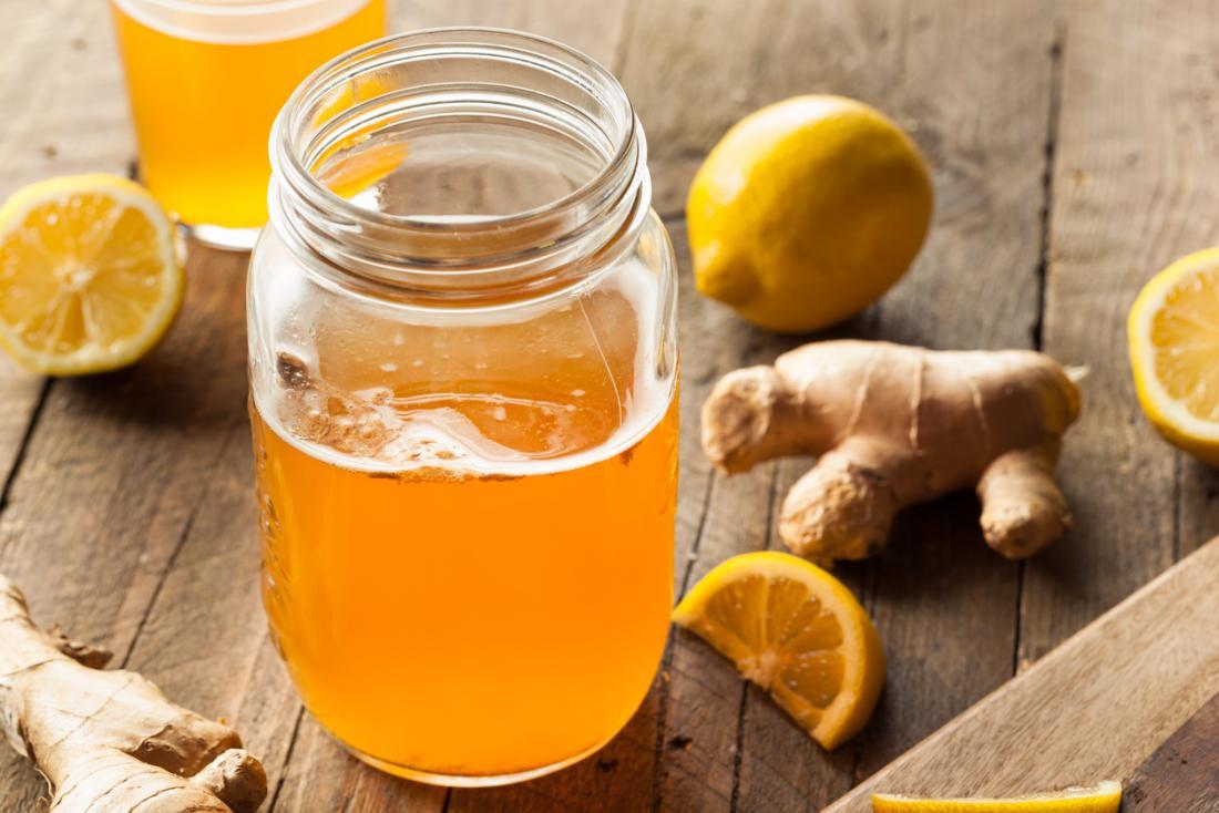 Doğranmış limon ve zencefil bir kök ile ahşap bir masa üzerinde ham kombucha fermente içecek bir kavanoz.