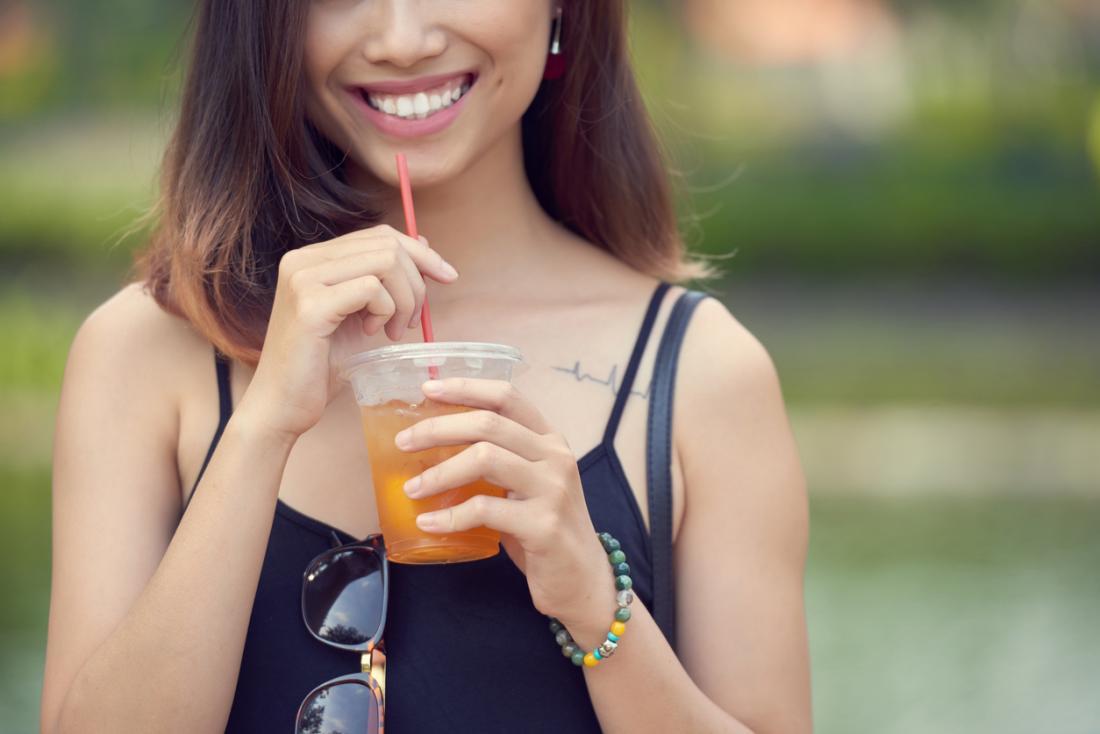 Meyve suyu buz çay içme genç gülümseyen kadın.