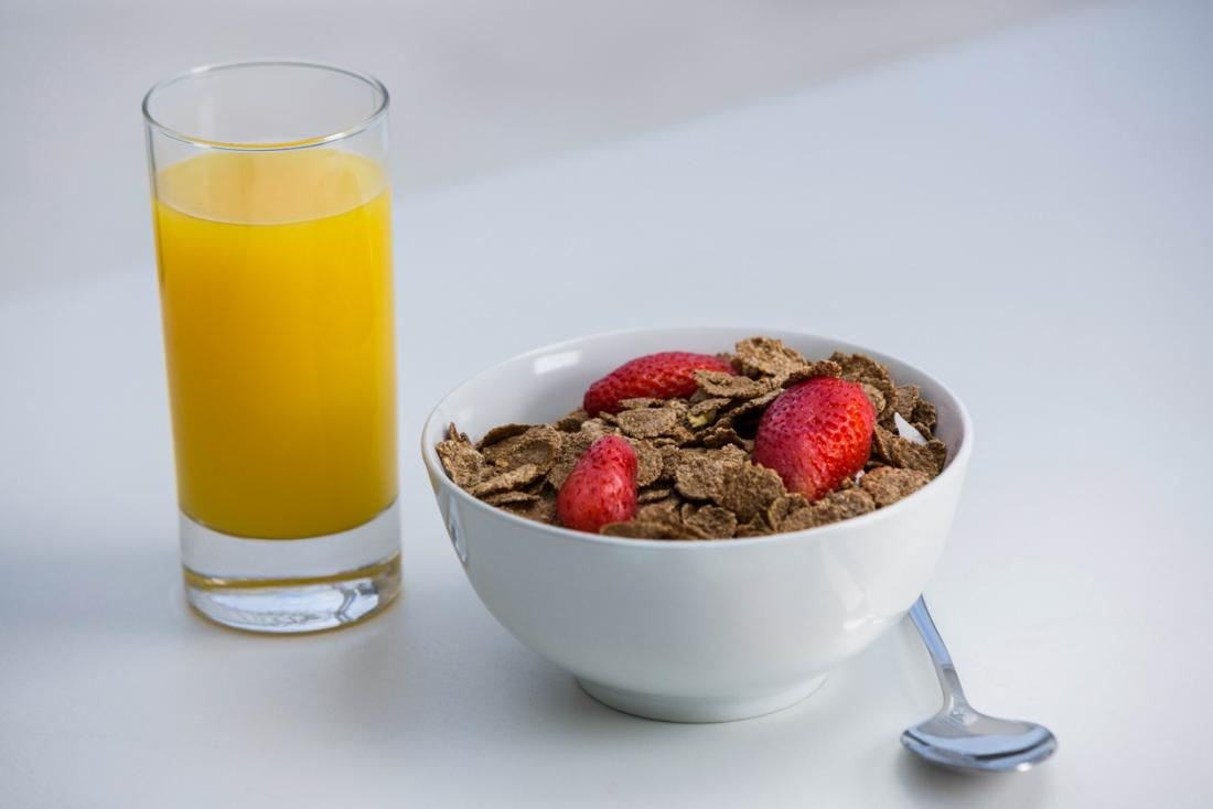 朝食のためのオレンジジュースのガラスの隣に、strwberriesの上にふすまのふすまの穀物のボウル。