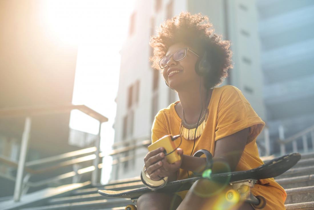 Người phụ nữ hạnh phúc cảm thấy tốt vì endorphins ngồi bên ngoài nghe nhạc.