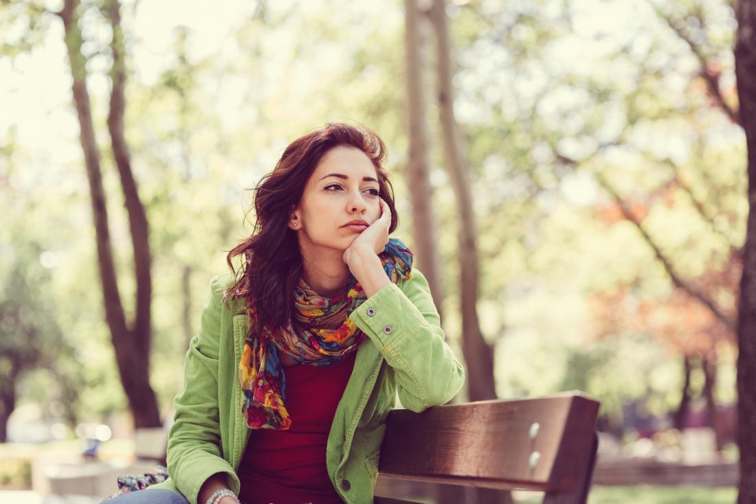 Người phụ nữ ngồi trên ghế đá công viên nhìn buồn và suy niệm.