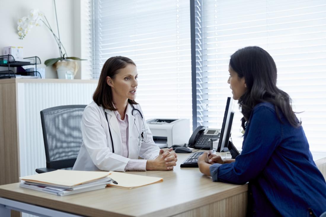 Patiente assise sur le bureau de la femme médecin, discutant du problème.
