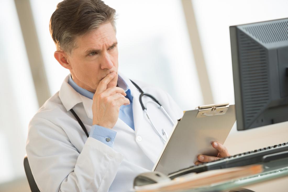 Доктор, който държи клипборда и гледа на екрана на компютъра.