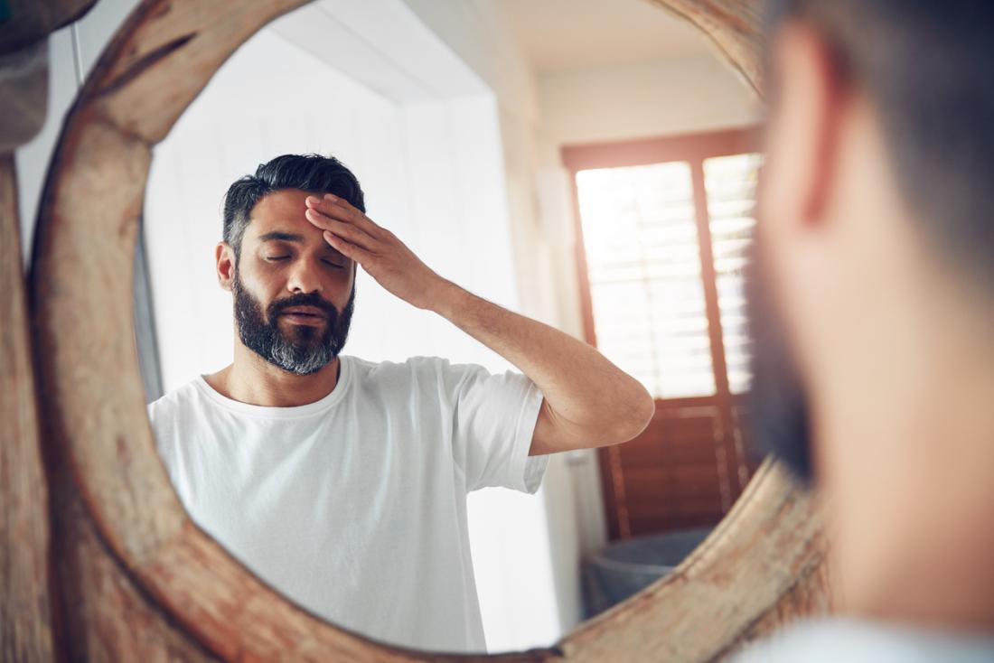 Mann, der seinen Kopf vor Spiegel hält