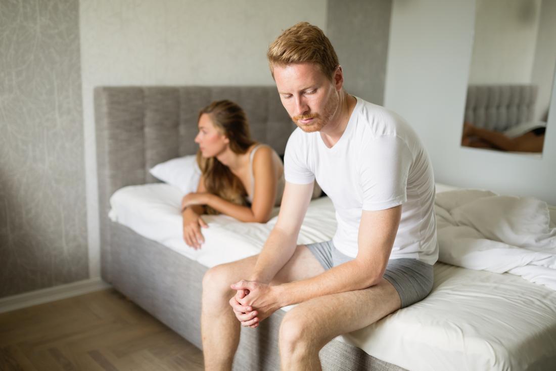 Homme avec dysfonction érectile assis sur le bord du lit avec une femme allongée en regardant de l'autre côté.