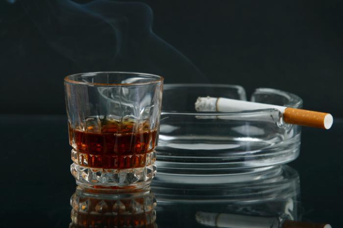 Napój alkoholowy i papieros spoczywający na popielniczce