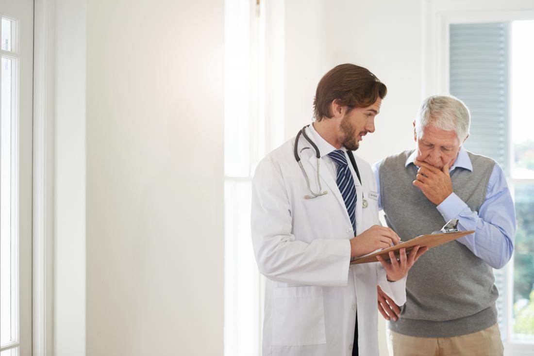 Yaşlı erkek hasta doktorun panosuna bakıyor.