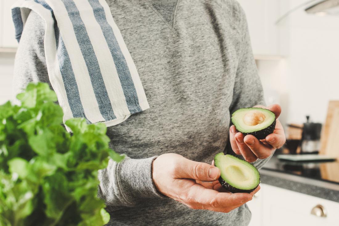 homem segurando abacate enquanto cozinha