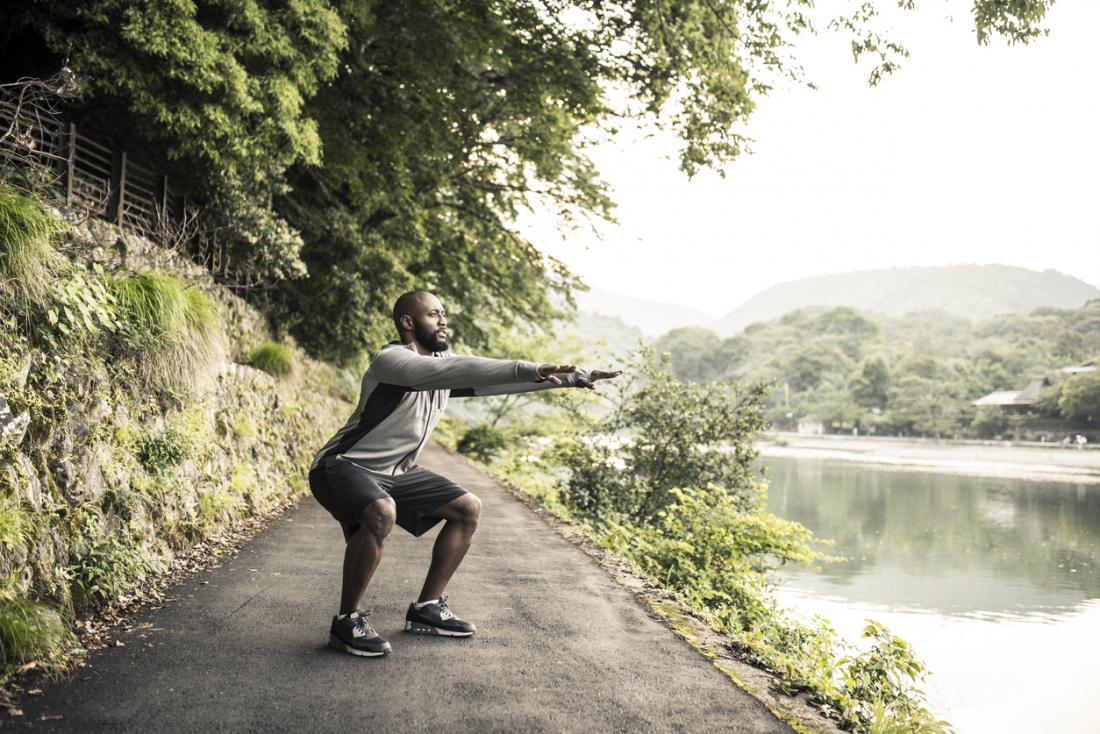 homem fazendo um agachamento em uma trilha
