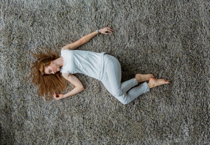 Femme allongée sur le sol.