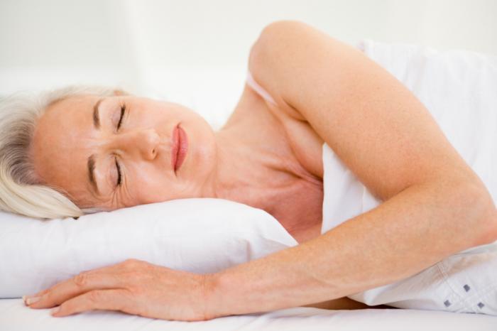 Une femme âgée s'endormir dans son lit.