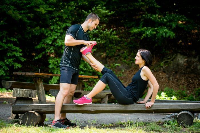 Une femme avec des crampes a la jambe étirée.