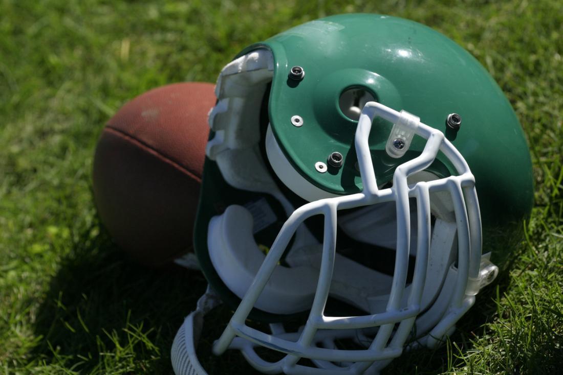 Um capacete e futebol deitado na grama.