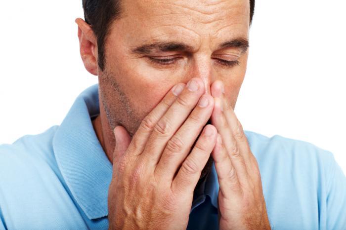 Un uomo tiene il naso con entrambe le mani