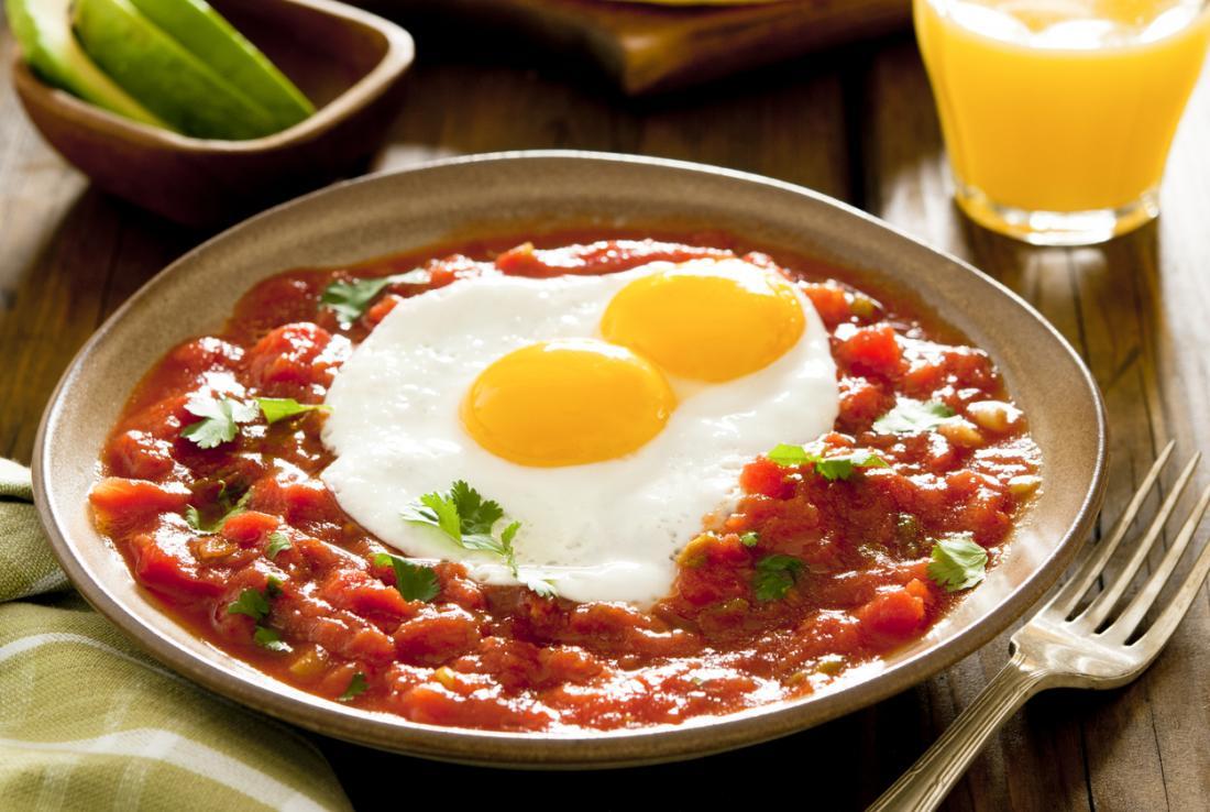 Huevos rancheros; trứng chiên đang nằm trên một chiếc giường sốt cà chua