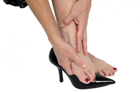 Femme apaisant ses pieds après avoir porté des talons hauts