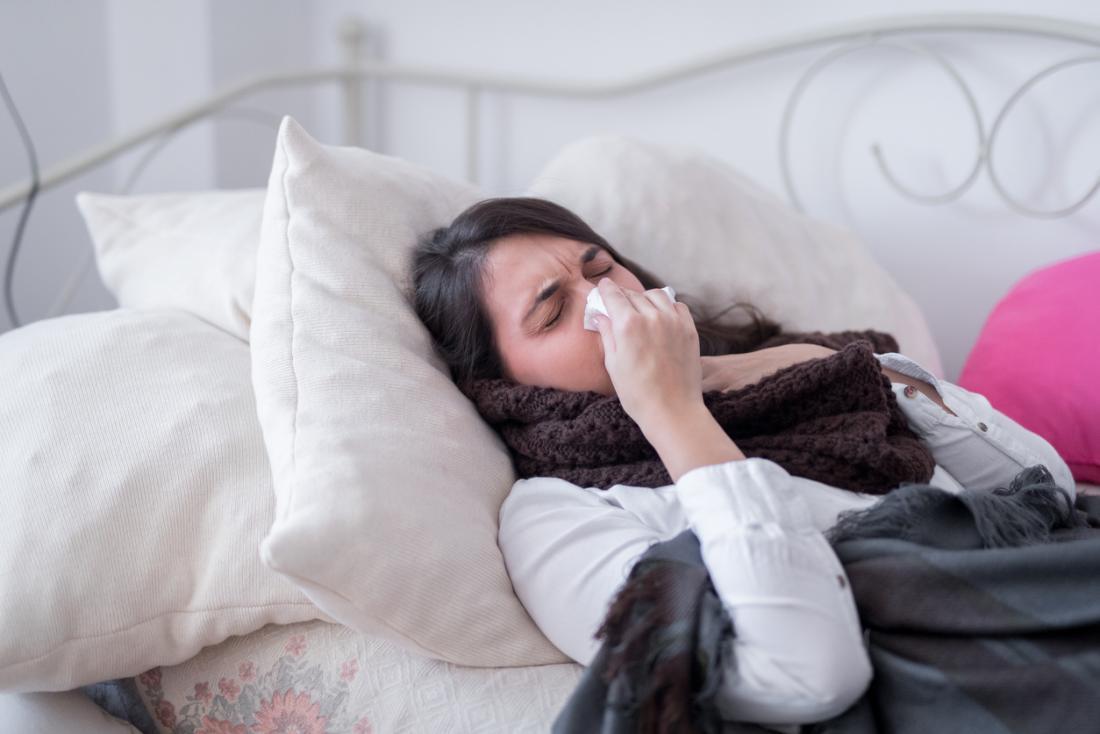 болна жена в леглото, която развява носа си