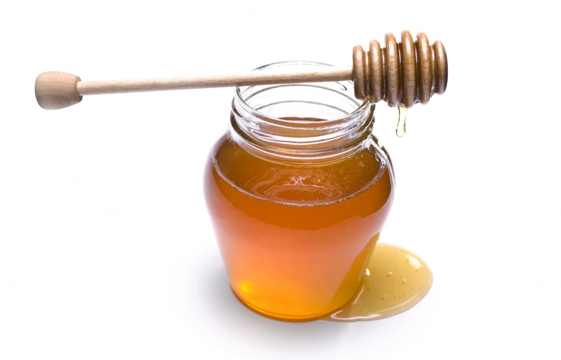 蜂蜜は、その健康上のメリットのために何千年も摂取されてきました。蜂蜜の上に木製のチョッパーを持つ蜂蜜の瓶。