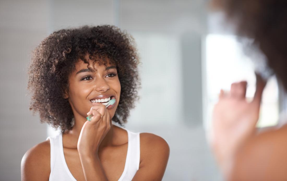 Frau putzt ihre Zähne im Spiegel