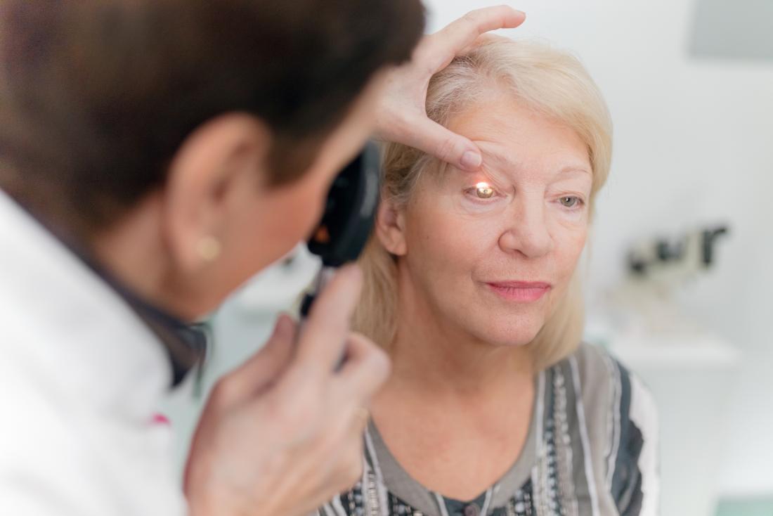 Bác sĩ nhãn khoa sử dụng kính soi đáy mắt để kiểm tra mắt của người phụ nữ trưởng thành.