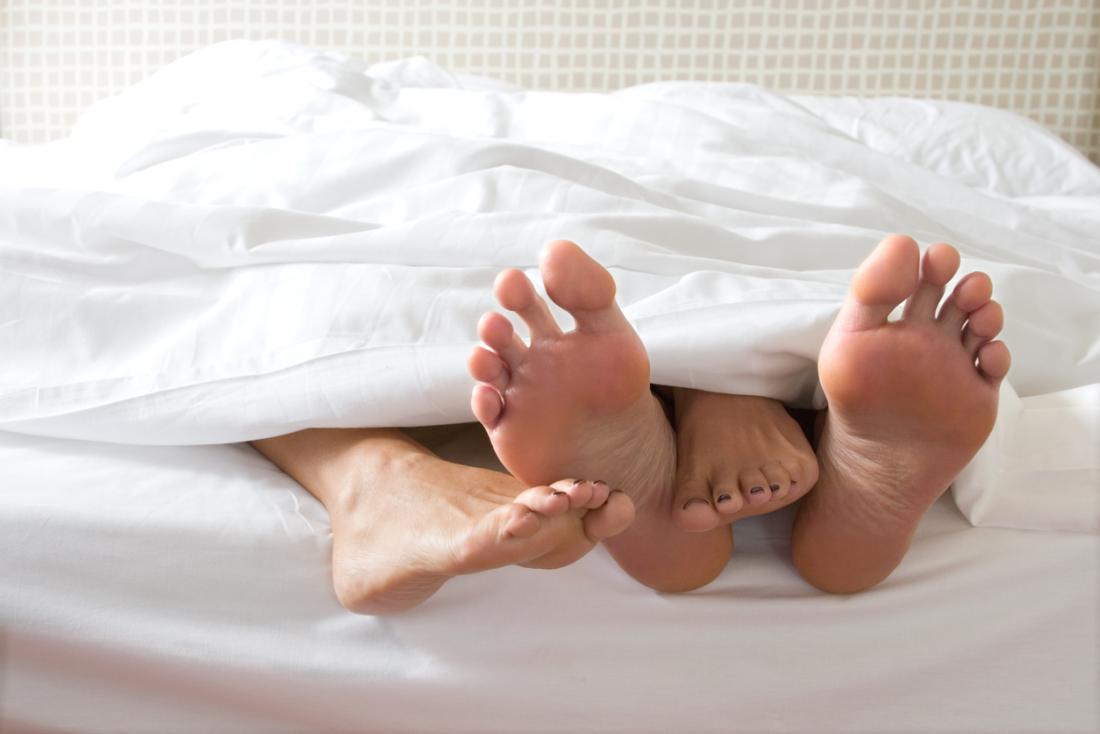 deux paires de pieds au bout d'un lit