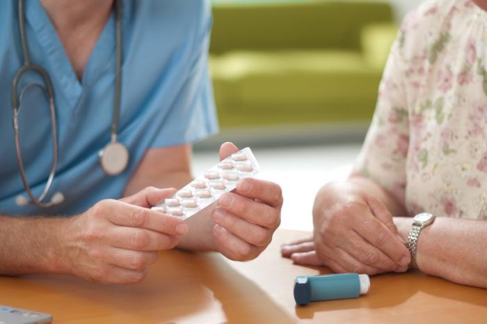 Specjalista medyczny omawia pigułki z osobą z inhalatorem.