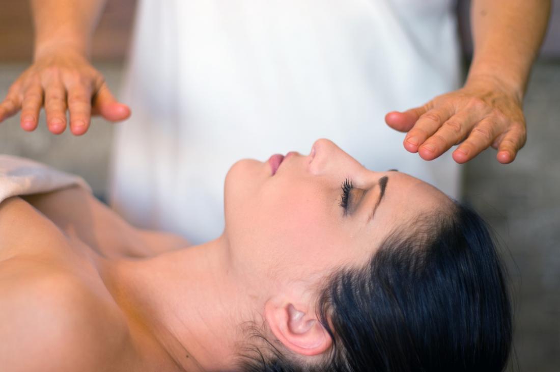 In Reiki überträgt der Praktizierende Energie, indem er seine Hände über oder auf den Patienten legt.