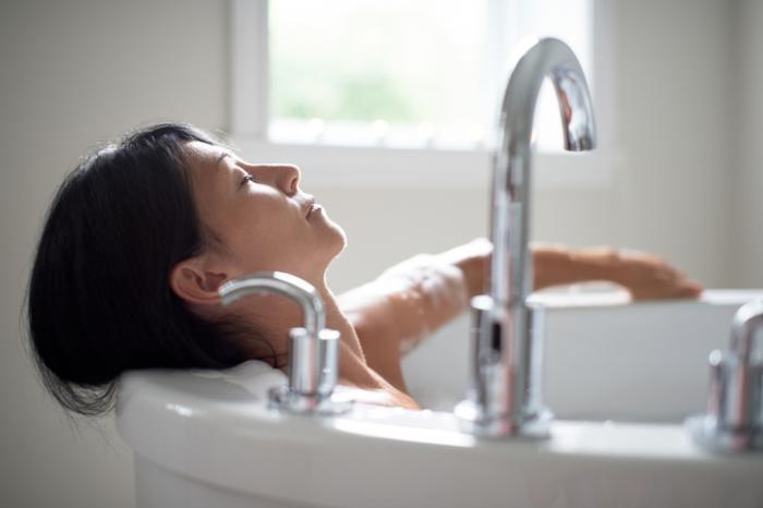 [mulher relaxando em um banho]