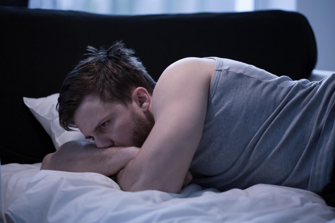 uomo sveglio nel letto con possibile sogno bagnato