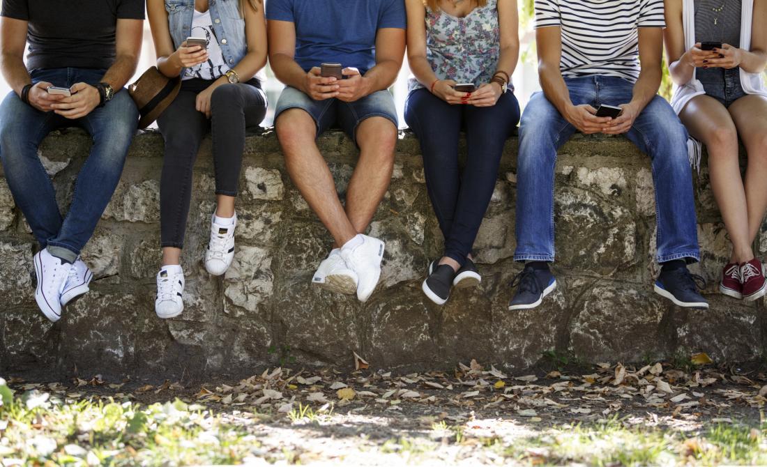 Adolescenti seduti su un muro con gli smart phone in mano