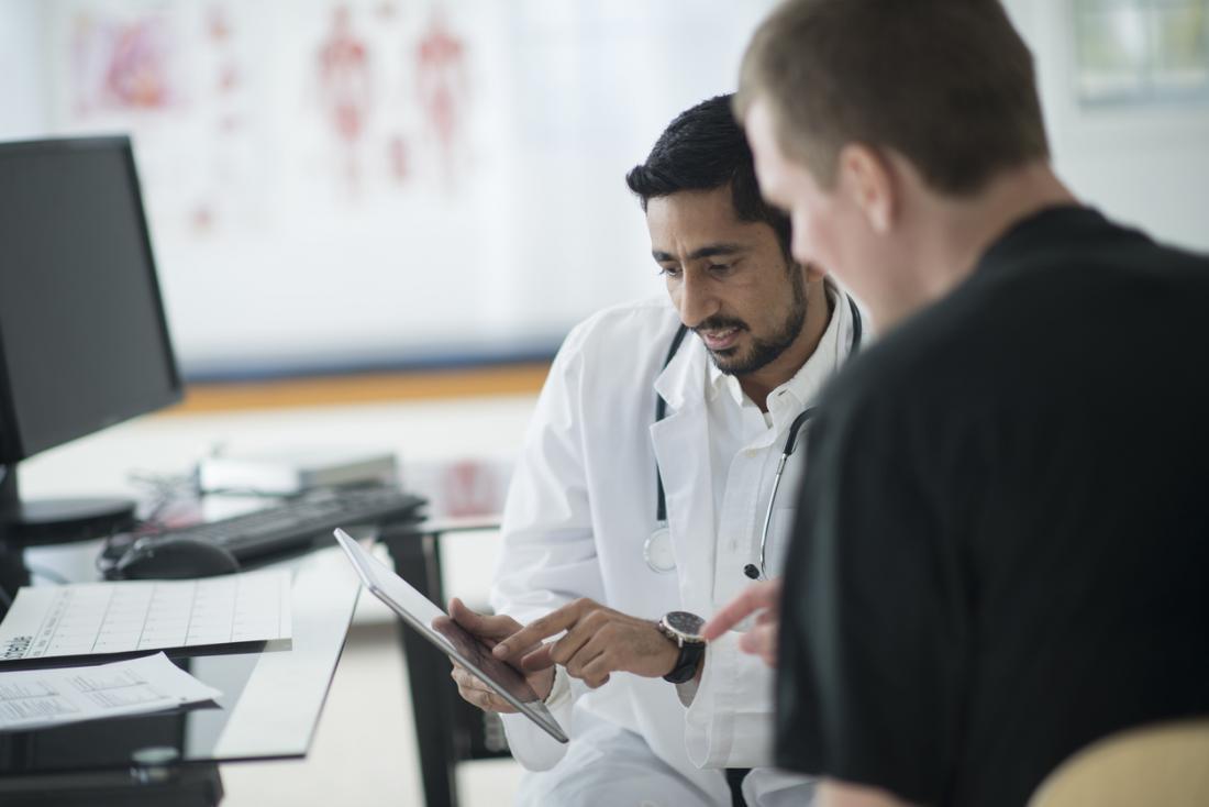 Médico mostrando notas ao paciente.