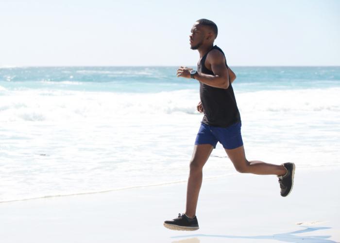 Man jogging su una spiaggia.