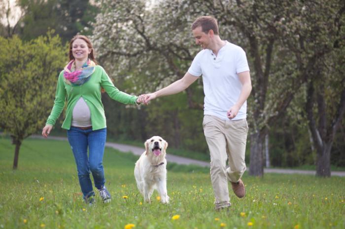 Una donna incinta e un uomo che cammina con un cane.