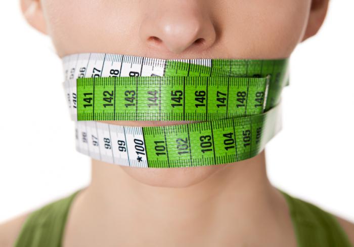 Una donna con un metro a nastro intorno alla bocca