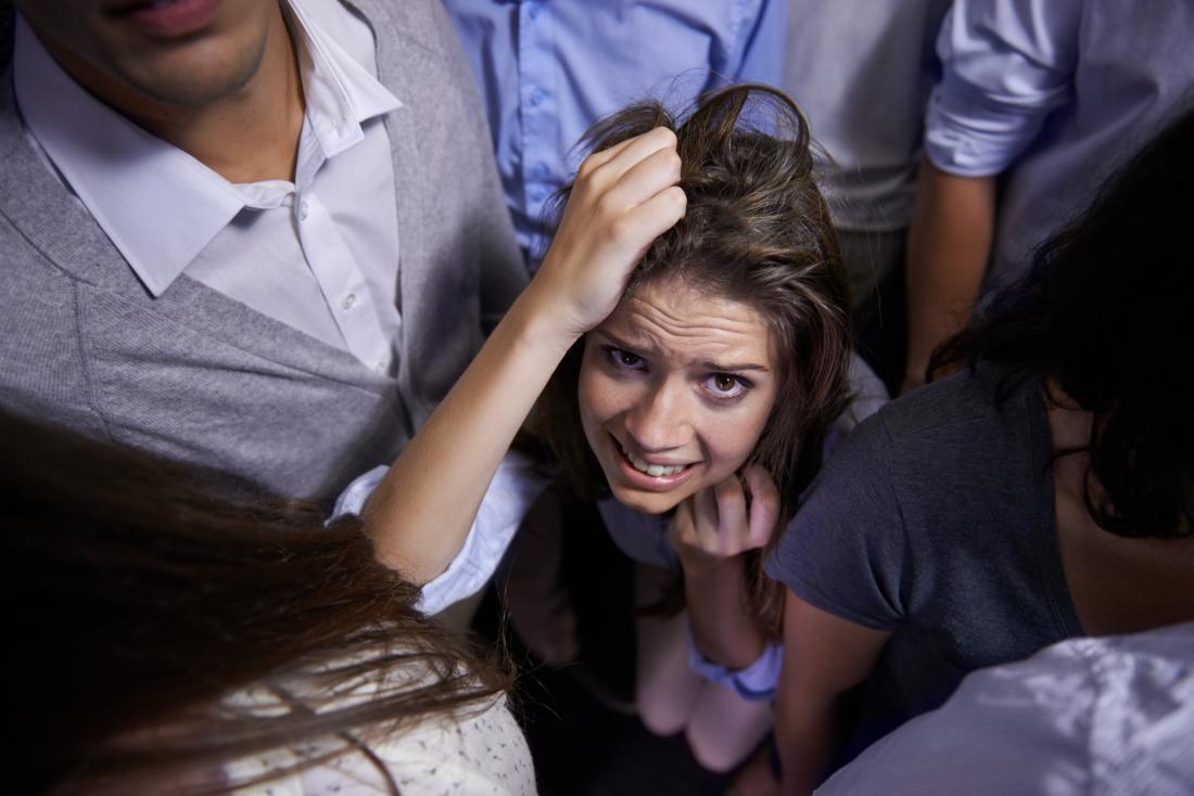 người phụ nữ trẻ lo lắng được bao quanh bởi những người
