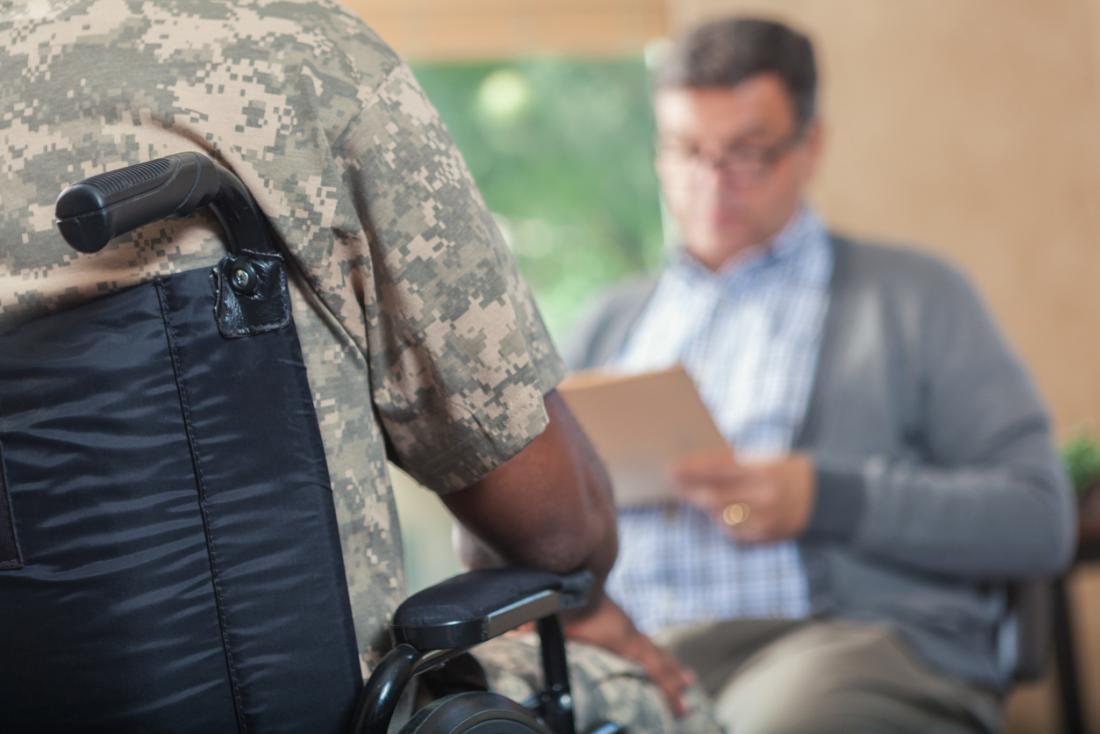 Veterano em cadeira de rodas com terapia com o conselheiro.