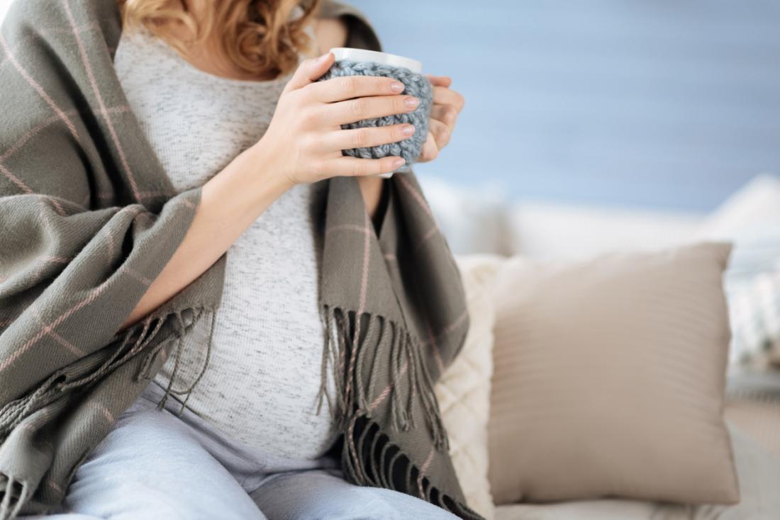 Femme enceinte avec une tasse de thé.