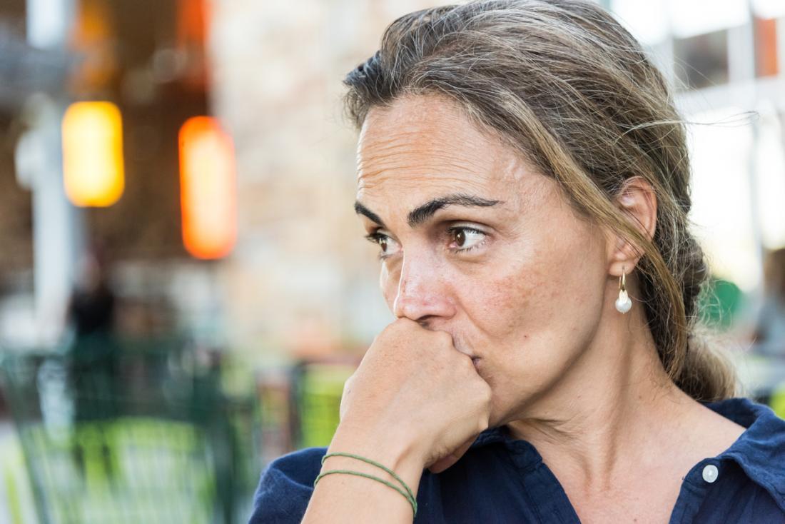 Възрастна жена, която преживява менопаузата, изглежда загрижена
